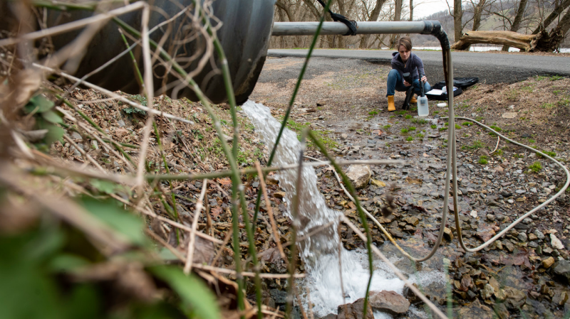 Image of Leigh-Anne Krometis examining a water source in rural Appalachia.