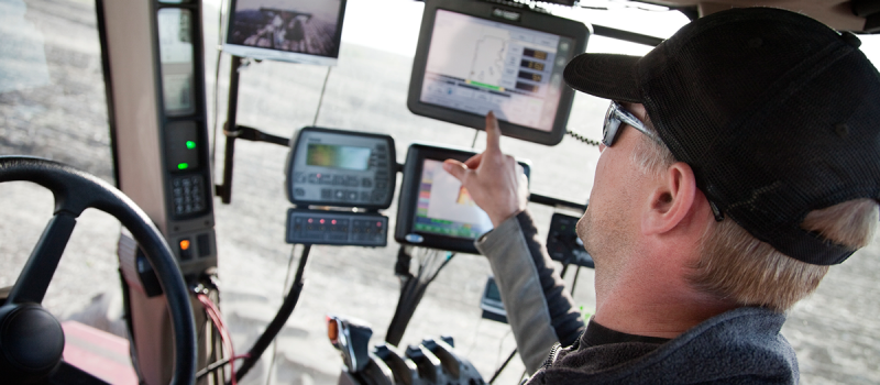 Image of a man in farm equipment pointing to screens in front of the passenger window.