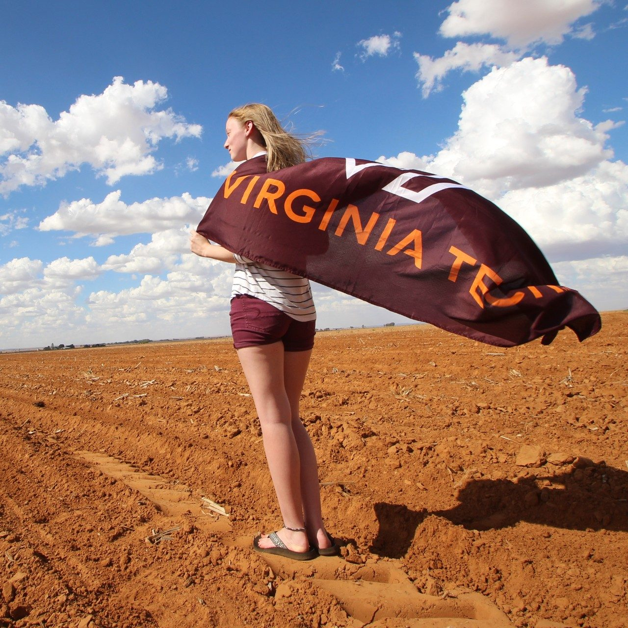 Student holding VT flag as a cape